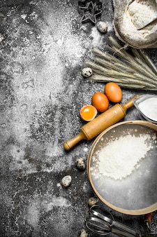Фон выпечки. ингредиенты и инструменты для приготовления теста. на деревенском фоне.