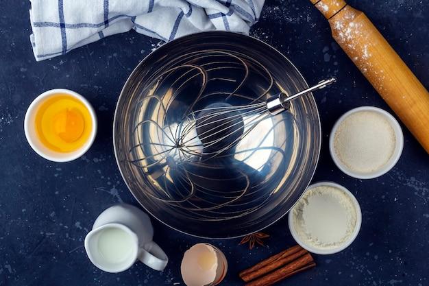 背景を焼きます。暗いテーブルでケーキを調理するための食材や調理器具。食品のコンセプト。