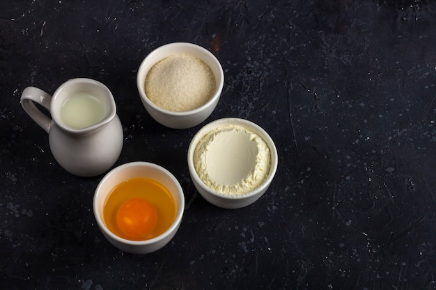 Baking background. ingredients for cooking cake (flour, egg, sugar, milk) in bowls on dark table. food concept. close up layout, copy space for text
