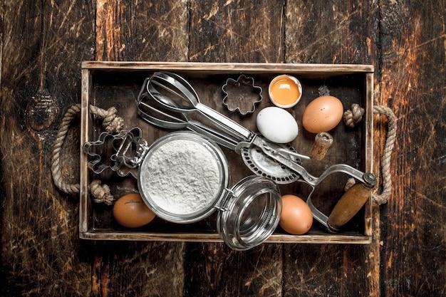 Фон выпечки. ингредиенты для свежего теста. на деревянном фоне.