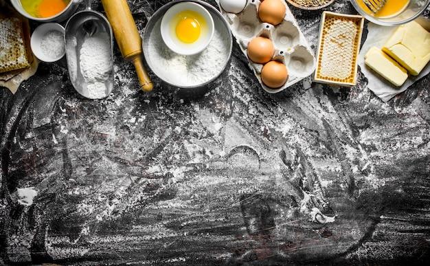 Фон выпечки. ингредиенты для приготовления теста в домашних условиях на деревенском столе