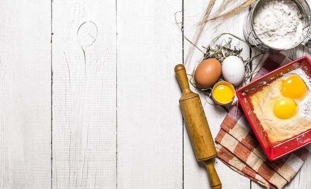 Фон выпечки ингредиенты для теста - яйцо, мука и скалка на белом деревянном фоне