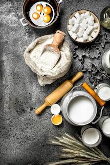 Фон выпечки. молоко, мука и другие ингредиенты для теста. на деревенском фоне.