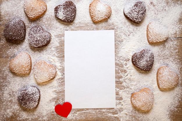 레시피 또는 메뉴에 대한 종이의 빈 시트와 베이킹 배경, 심장 모양의 쿠키