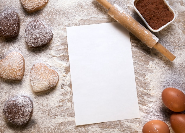 Baking background with blank sheet of paper for the recipe or menu, heart shaped cookies, eggs, flour and rolling pin. empty space for text. valentines day