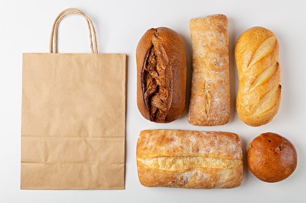 Baking background with eco disposable paper bag and loaves of bread top view on gray background with mockup