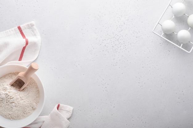 흰색 대리석 테이블에 밀가루, 계란, 주방 도구, 기구, 쿠키 금형으로 배경을 굽습니다. 평면도. 플랫 레이 스타일. 조롱.