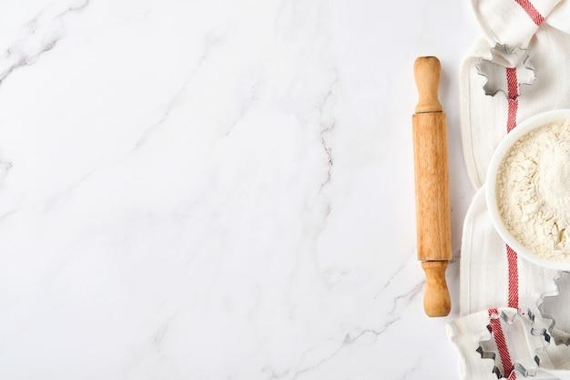 Фон выпечки с мукой, яйцами, кухонными принадлежностями, посудой и формами для печенья на белом столе