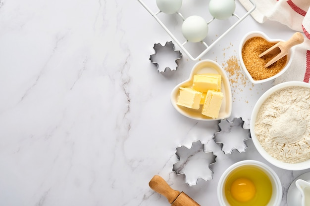 Baking background with flour, eggs, kitchen tools, utensils and cookie molds on white  table