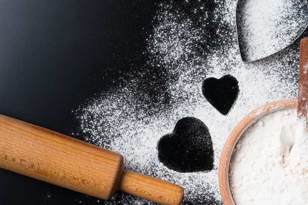 Baking background with flour, rolling pin and heart shape on a dark table with copy space, top view, flat lay. valentines day cooking concept