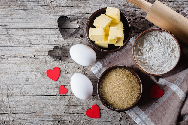 Baking background with flour, sugar, butter, rolling pin, eggs, and heart shape