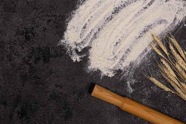 あなたのテキストのための空きスペースで背景を焼く。ボウルに小麦粉、黒いテーブルに卵と小麦