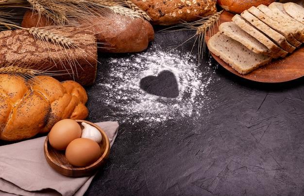 어두운 테이블에 심장 모양 및 밀가루와 음식 재료와 베이킹 배경. 어두운 배경에 호밀 빵의 다양한. 텍스트를위한 공간을 복사합니다. 요리를 좋아합니다. 밀가루의 심장, 흰 빵