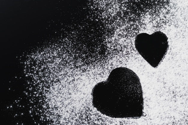 Baking background with heart shape and flour on a dark table with copy space