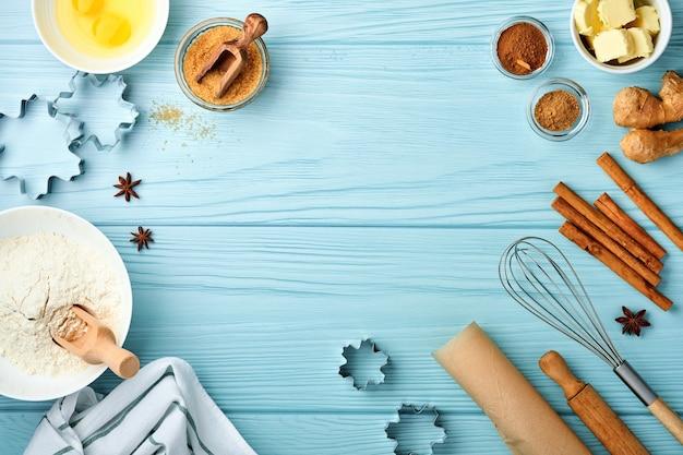 Фон выпечки с ингредиентами для приготовления имбирной муки, яиц, кухонных принадлежностей, посуды и форм для печенья на синем деревянном столе. вид сверху. плоский стиль. макет. рождественская выпечка.