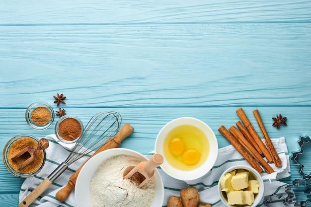 푸른 나무 테이블에 진저브레드 가루, 계란, 주방 도구, 기구, 쿠키 틀을 만들기 위한 재료로 배경을 굽습니다. 평면도. 플랫 레이 스타일. 조롱. 크리스마스 베이킹.