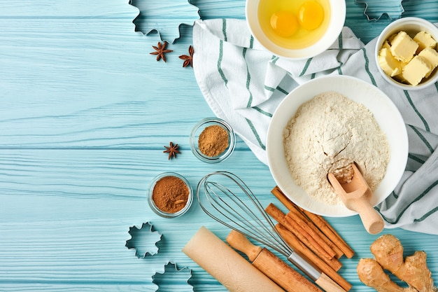 Baking background with ingredients for making gingerbread flour, eggs, kitchen tools, utensils and cookie molds on blue wooden table. top view. flat lay style. mock up. christmas baking.