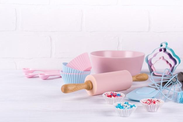 キッチンツールと背景を焼く:めん棒、木製のスプーン、泡立て器、ふるい、耐熱皿、白い木製の背景に形クッキーカッター。