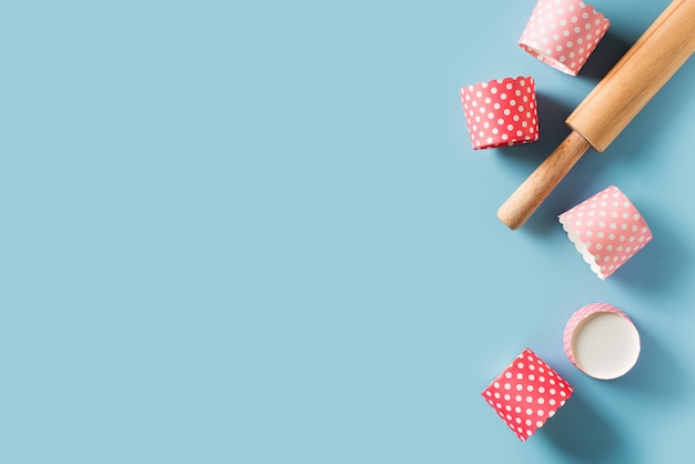 Baking background with pink cake forms on blue background