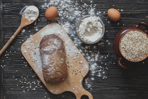 Baking bread at home on a rustic wooden table with space for text layout. top view