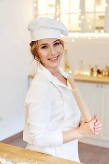 シェフによるベーキング。キッチンでめん棒を持った白い帽子をかぶった女性