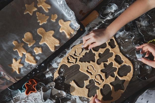 ダークブラウンの木製テーブルでクリスマスクッキーを焼く。家族でジンジャーブレッドマンを作り、ジンジャーブレッド生地のクッキーを切り、上からの眺め。