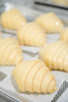 自宅でクラシックなクロワッサンを焼き、未調理のクロワッサンに卵を刷毛で塗ります。