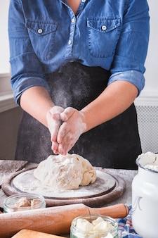 Концепция выпечки. мука, молоко и яйца на деревянной разделочной доске, ингредиенты для выпечки. обрезанное изображение до неузнаваемости женщины месить и посыпать дрожжевое тесто для пиццы. женский пекарь крупным планом, вертикальный