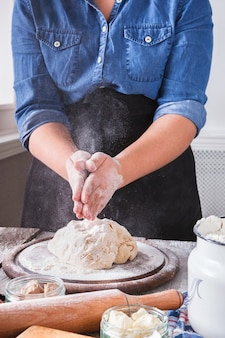 Baking concept. flour, milk, and eggs on wooden cutting board, pastry ingredients. cropped image of unrecognizable woman knead and sprinkle yeast pizza dough. female baker closeup, vertical