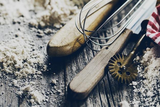 ベーキングコンセプトキッチンは、小麦粉と木製の背景に焼くためのカトラリーアクセサリー。閉じる。クッキングプロセス。