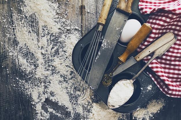 Концепция выпечки кухня приготовления столовых приборов аксессуары для выпечки на деревянном фоне с мукой. вид сверху. процесс приготовления. никто.