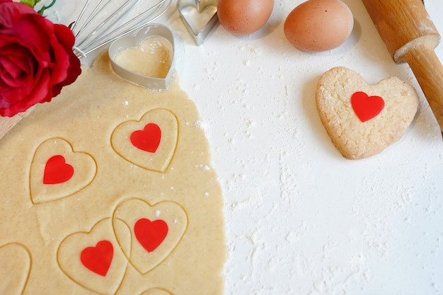 Baking concept for st. valentines day with heartshaped cutters and eggs on white wooden table with red flower rose, copy space