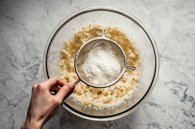 Выпечка печенья. добавляем в тесто муку, разрыхлитель и соль в большой стеклянной миске. горизонтальное фото, вид сверху.