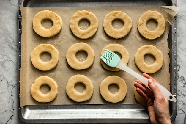Выпечка печенья. смажьте круглое печенье яичным белком на противне с пергаментной бумагой. горизонтальное фото, вид сверху.