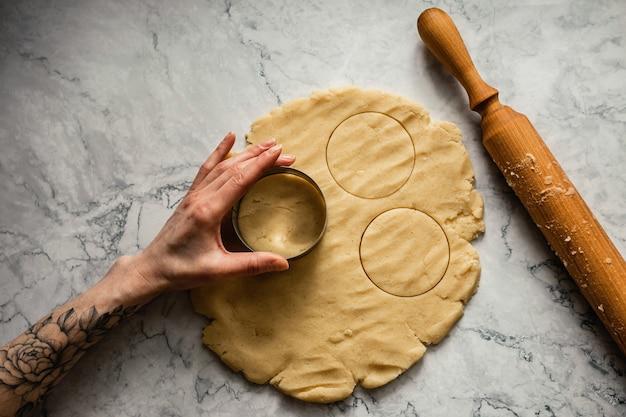 Выпечка печенья. вырезание круглого печенья резаком на мраморном фоне. деревянная скалка. горизонтальное фото, вид сверху.