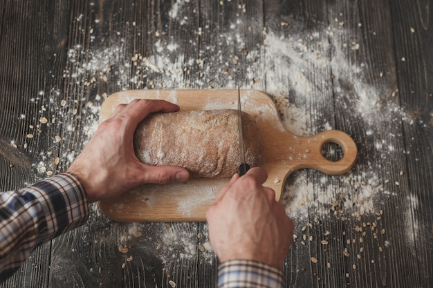 Baking and cooking concept background. hands of baker closeup cutting bread loaf with knife on rustic wooden table sprinkled with flour.