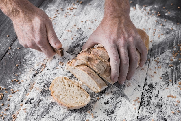 Baking and cooking concept. hands of baker slicing bread loaf with knife on rustic wooden table sprinkled with flour. stained dirty hands of cook.