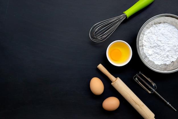 Выпечка приготовления ингредиентов на черном фоне. вид сверху