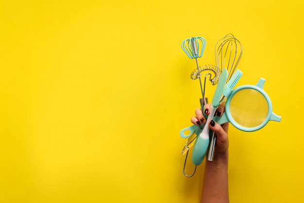 Baking flat lay. female hands holding kitchen tools, sieve, rolling pin, spatula and bruch on yellow background. banner with copy space