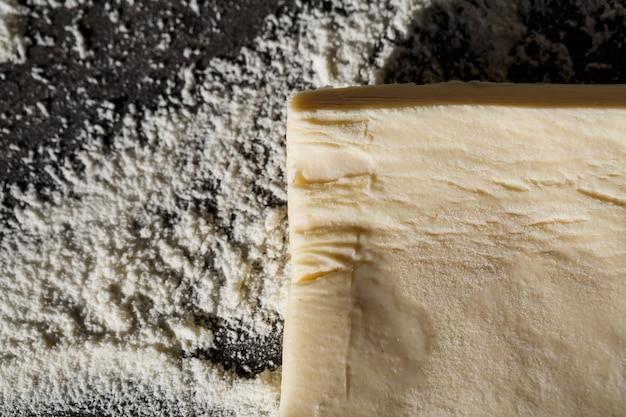 平らに焼くと、生地がテーブルの上に置かれ、灰色の背景に小麦粉が置かれます。ベーキングメニュー、レシピ、ホームベーキングのコンセプト。テキストのコピースペースを含む上面図。