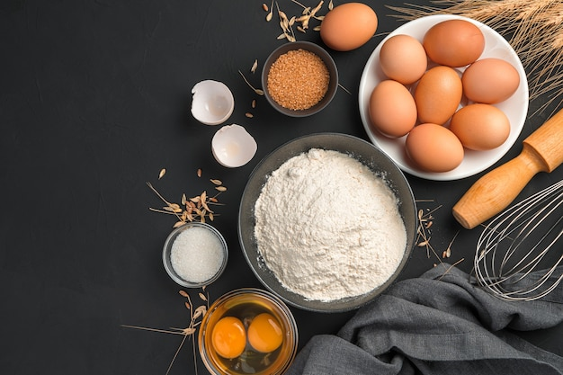 ベーキング、小麦粉、卵、砂糖、コピーするスペースのある黒い背景に麺棒。料理の背景。上面図。