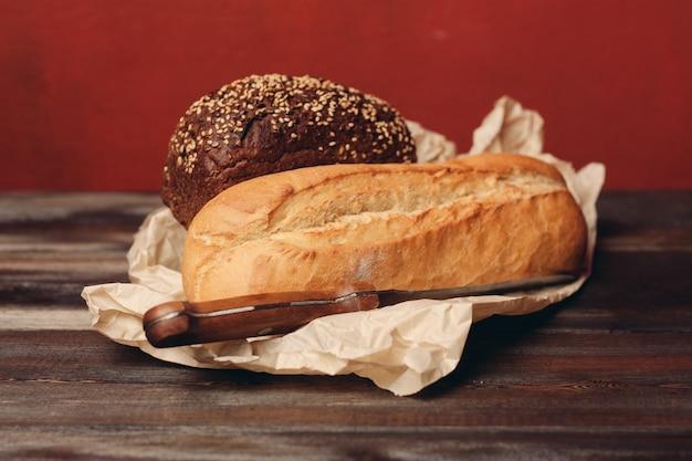 小麦粉製品のパンを紙の包装の鋭いナイフと木製のテーブルに焼きます