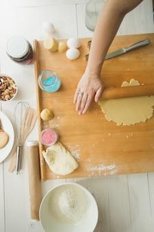 나무 테이블에 베이킹 재료 쿠키용 반죽 만들기