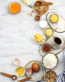 トレンディな明るい大理石の背景に材料とツールを焼く。小麦粉、卵、砂糖、ミルク、バター、レイアウト、フラットレイ上面図コピースペース