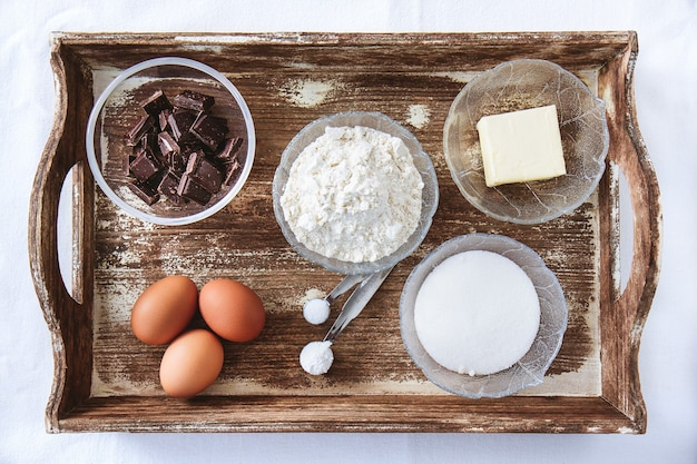 Baking ingredients for chocolate cake muffins or cookies lying ready on wooden kitchen tray