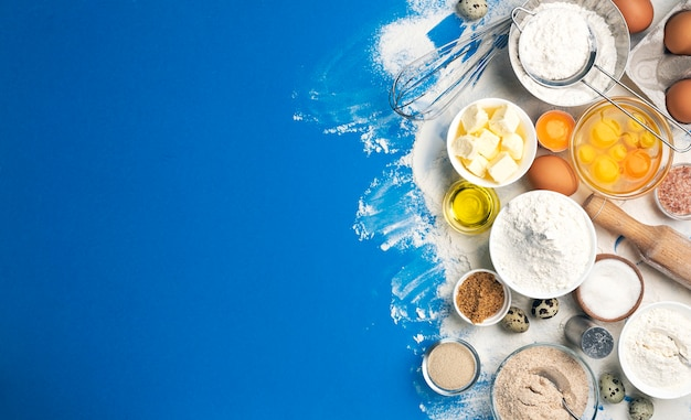 Baking ingredients for dough on blue color background, top view of flour, eggs, butter, sugar and kitchen utensils for homemade baking. cooking concept banner with copy space for text Premium Photo