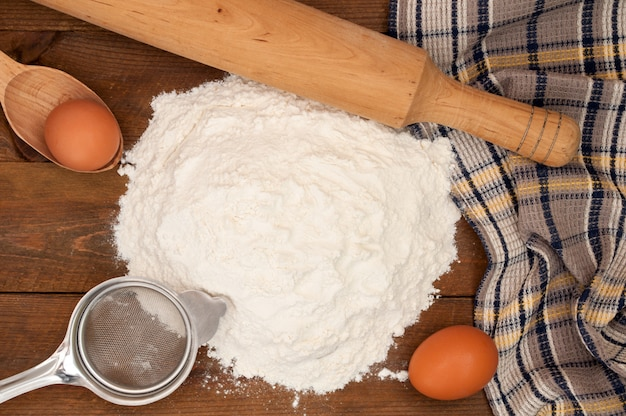 Baking ingredients: egg and flour, sieve and rolling pin on wooden background.