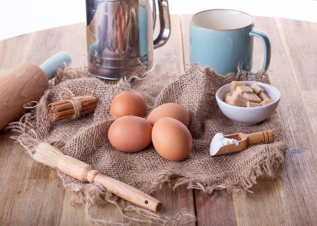 木製のテーブルで焼くためのベーキング材料卵、砂糖、ベーキングパウダー、シナモン