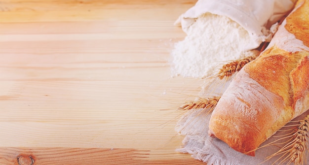 Baking ingredients: flour and ears on a light wooden background