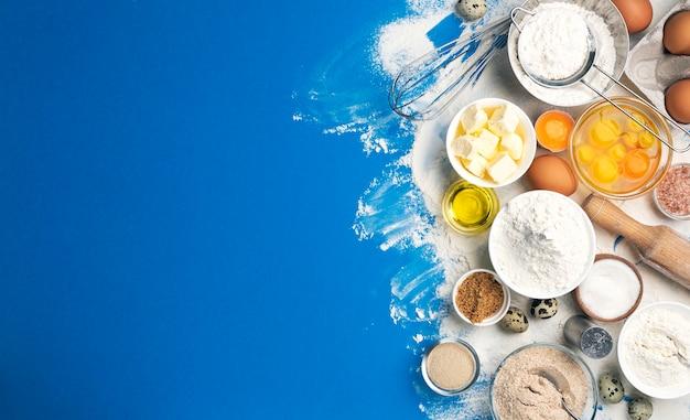 Ингредиенты для выпечки теста на синем цветном фоне, вид сверху муки, яиц, масла, сахара и кухонной утвари для домашней выпечки. баннер концепции приготовления пищи с копией пространства для текста